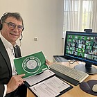 """Dr. Volker Jung in seinem Büro vor seinem Computer mit Plakat """"Churches for Future"""" in seiner Hand"""